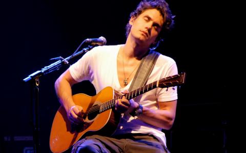 john mayer playing guitar wearing a watch