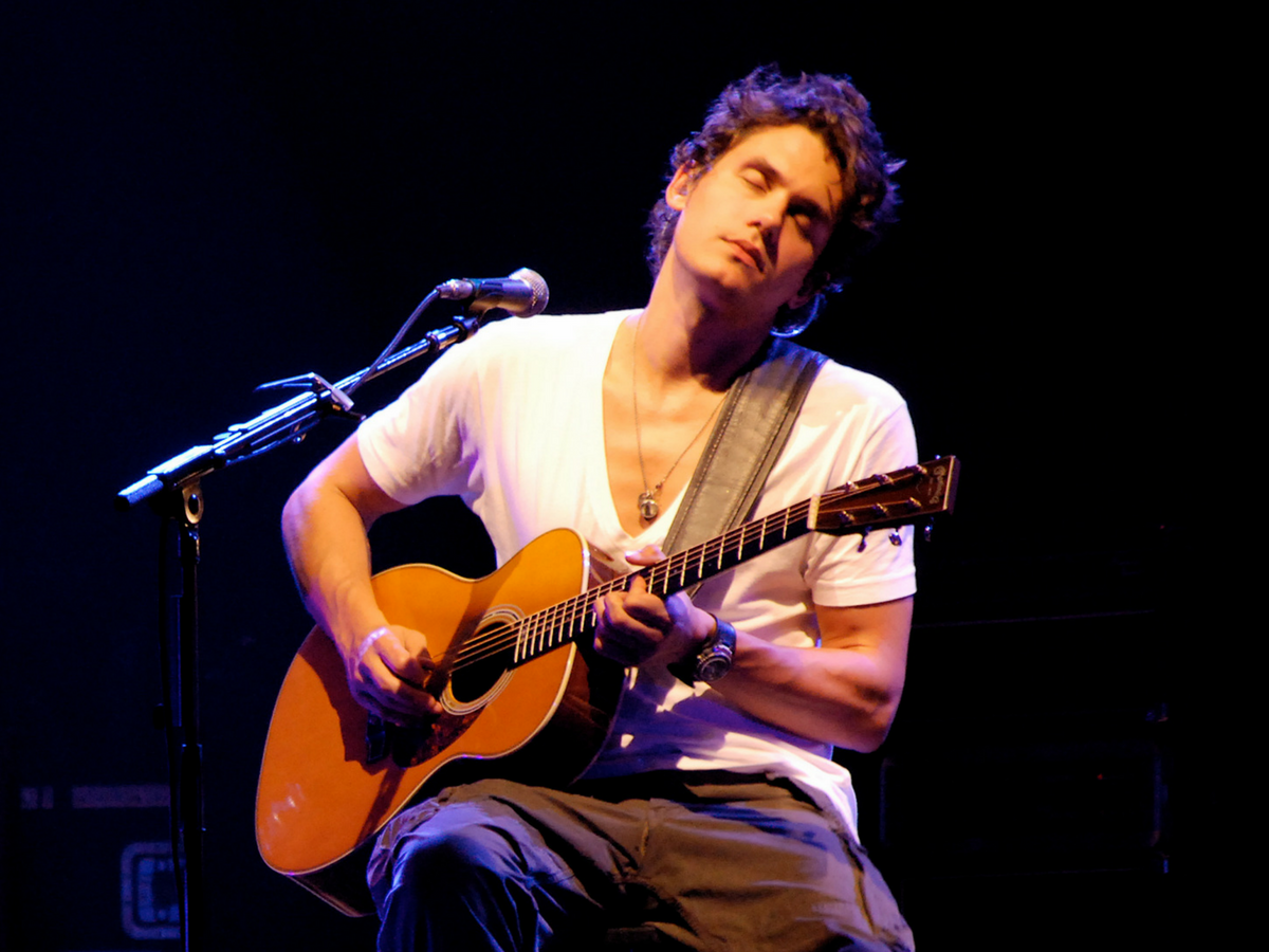 john mayer playing guitar wearing a watch